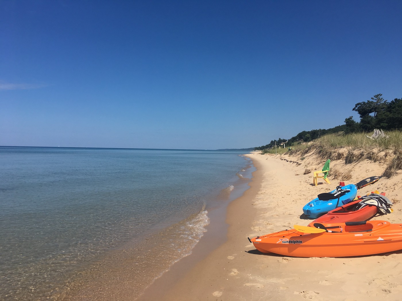 Kayaks rest on the shore of Lake Michigan against a brilliant blue sky